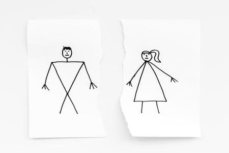 離婚または崩壊の概念。白い背景の上面図に描かれた男女との紙の破れたシート。