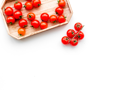 Fresh red cherry tomatoes in wooden tray on white background top view.