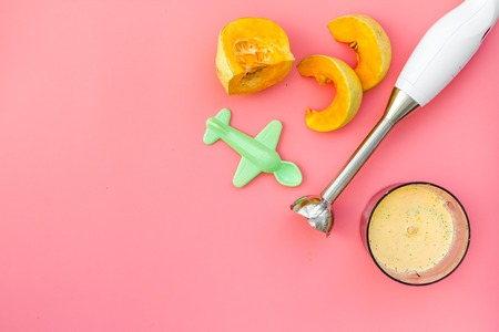 Make baby food at home. Puree with pumpkin near immersion blender, toy on pink background top view.