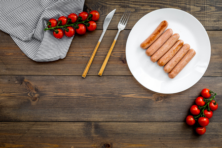 Main dish for a picnic. Grilled sausages near cherry tomatoes on dark wooden table top view.