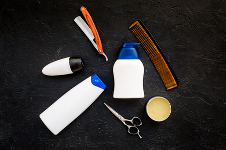 Mens set for everyday body, facial and hair care. Shampoo, gel, tools for brushing, scissor, comb on black background top view. Stockfoto