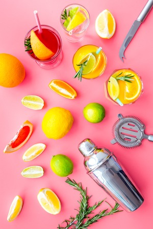 Mix exotic fruit cocktail with alcohol. Shaker and strainer near citrus fruits and glass with cocktail on pink background top view. 스톡 콘텐츠
