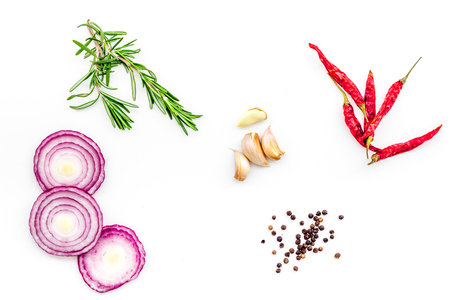 Red onion rings as seasoning. Onion near chili pepper, rosemary, black pepper, garlic on white background top view.