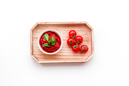 Tomato sauce in bowl with green basil near cherry tomatoes in wooden tray on white background top view copy space Фото со стока