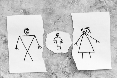 Child suffers from a divorce. Torn sheet of paper with drawn man, woman and child on grey background top view.