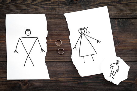 Child suffers from a divorce. Torn sheet of paper with drawn man, woman and child, wedding rings between parts on dark wooden background top view. Stock fotó - 99601380