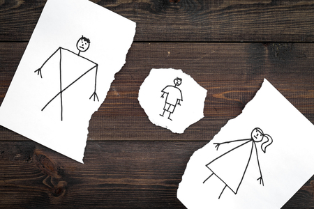 Child suffers from a divorce. Torn sheet of paper with drawn man, woman and child on dark wooden background top view. Stock Photo - 99600959