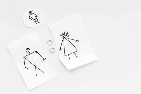 子供は離婚に苦しんでいる。描かれた男性、女性と子供と紙の破れたシート、白い背景のトップビュー上の部分の間の結婚指輪。 写真素材