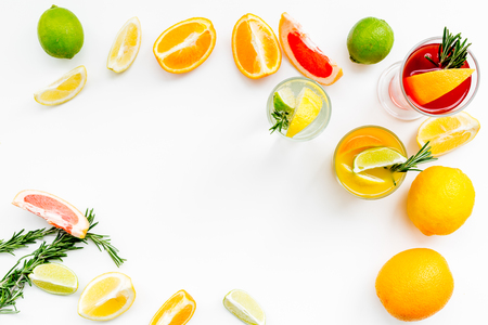 Concept of alcoholic cocktail with fruits. Glass with beverage near oranges, grapefruit, lime and rosemary on white background top view.