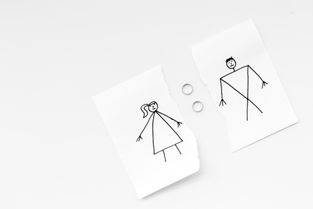 Divorce or falling apart concept. Torn sheet of paper with drawn man and woman, wedding rings between parts on white background top view . Stock fotó