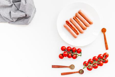 Grilled sausages on white table near cherry tomatoes and spices in wooden spoons top view. Banco de Imagens