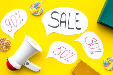 Sale concept with megaphone. Declare the sale. Electronic megaphone near word sale in cloud, gift boxes and sweets on yellow background top view.