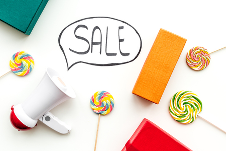 Sale concept with megaphone. Declare the sale. Electronic megaphone near word sale in cloud, gift boxes and sweets on white background top view.