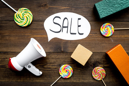 Sale concept with megaphone. Declare the sale. Electronic megaphone near word sale in cloud, gift boxes and sweets on dark wooden background top view.