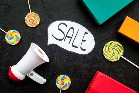 Sale concept with megaphone. Declare the sale. Electronic megaphone near word sale in cloud, gift boxes and sweets on black background top view.