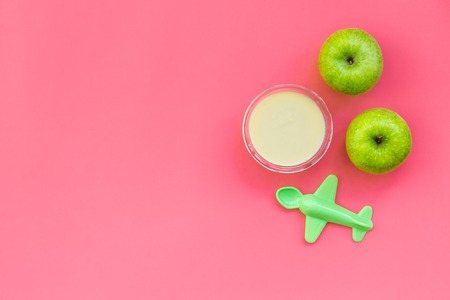 Healthy food for little baby. Apple puree with near toys on pink background top view.