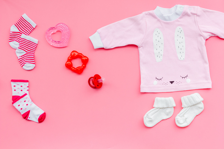 Clothes for small girl with booties on pink background top view