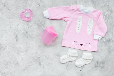 af67a4d48a4c Clothes for small girl with booties on grey background top view copy space