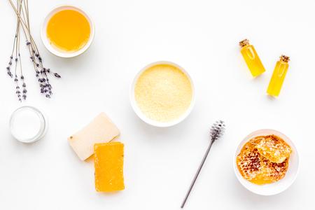 Homemade cosmetics with honey. Handmade soap, spa salt, cream on white background top view Stock Photo