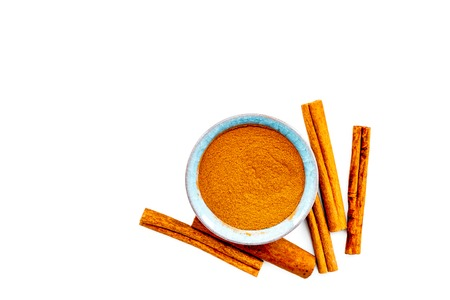 Cinnamon seasoning. Sticks and powder on white background top view copy space