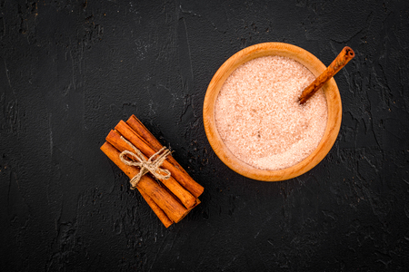 Cinnamon for cooking. Cinnamon sticks near bowl with sugar on black background top view copy space Banco de Imagens