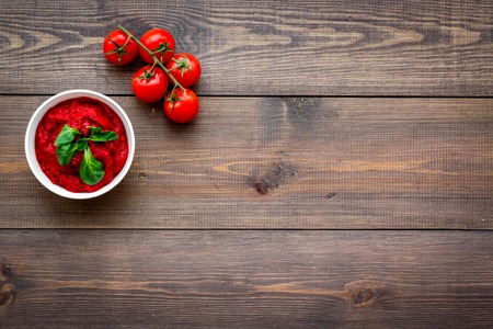 Tomato sauce in bowl with green basil near cherry tomatoes on dark wooden background top view copy space