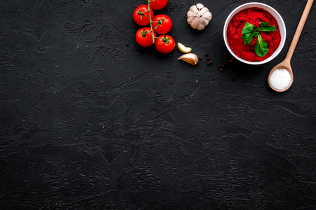 Ingredients for tomato sauce. Cherry tomatoes, garlic, green basil, black pepper, salt in spoon on black background top view space for text