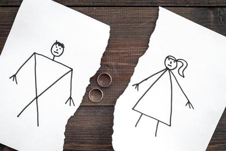 離婚または崩壊の概念。描かれた男女との紙の破れたシート、暗い木製の背景トップビュー上の部品間の結婚指輪