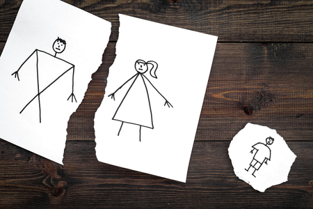 Child suffers from a divorce. Torn sheet of paper with drawn man, woman and child on dark wooden background top view copy space 写真素材