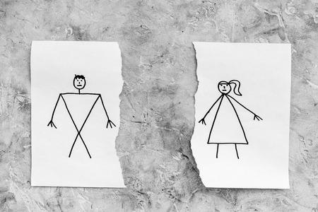 離婚または崩壊の概念。灰色の背景の上面図に描かれた男女と紙の破れたシート 写真素材