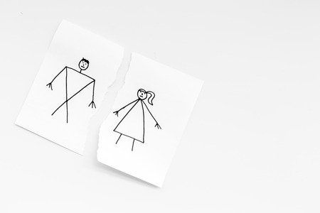 Divorce or falling apart concept. Torn sheet of paper with drawn man and woman on white background top view copy space