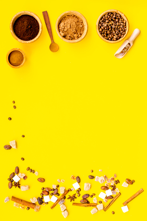 Ingredients for bakery and desserts. Cinnamon, cocoa, coffee, sugar, spices on yellow background top view space for text Banco de Imagens