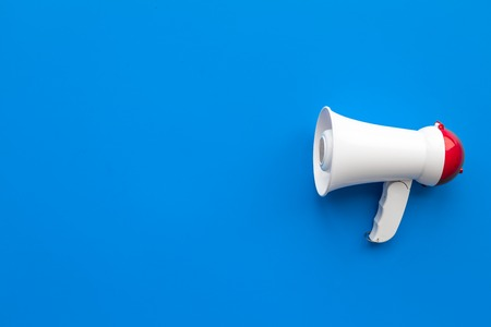 Attract attention concept. Megaphone on blue background top view copy space