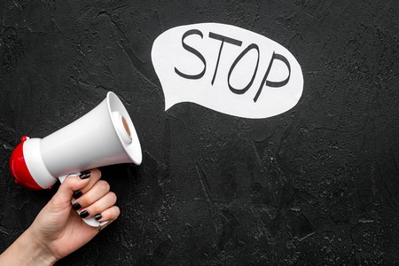 Demand to stop concept. Megaphone near cloud with word stop on black background top view space for text