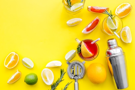 Mix exotic fruit cocktail with alcohol. Shaker and strainer near citrus fruits and glass with cocktail on yellow background top view space for text