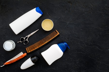 Mens set for everyday body, facial and hair care. Shampoo, gel, tools for brushing, scissor, comb on black background top view copy space