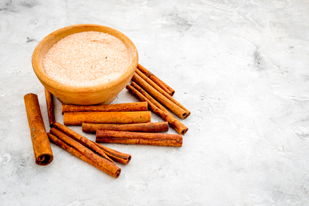 Cinnamon for cooking. Cinnamon sticks near bowl with sugar on grey background.