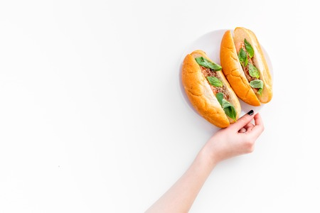 Hand takes homemade hot dogs with grilled sausages and greenery on white background top view. Banco de Imagens