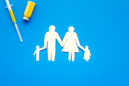 Vaccination as way to save healthy family. Syringe with colored vaccine near silhouette of family on blue background top view.