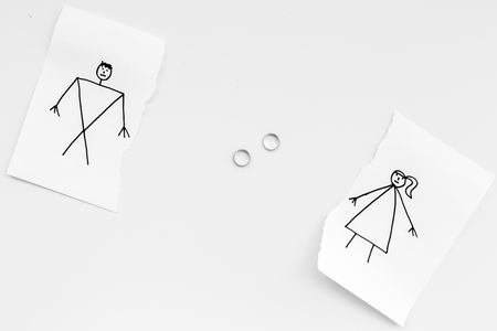 Divorce or falling apart concept. Torn sheet of paper with drawn man and woman, wedding rings between parts on white background top view . Stock Photo - 99773556