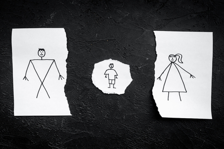 Child suffers from a divorce. Torn sheet of paper with drawn man, woman and child, wedding rings between parts on black background top view. Stock Photo - 99773557
