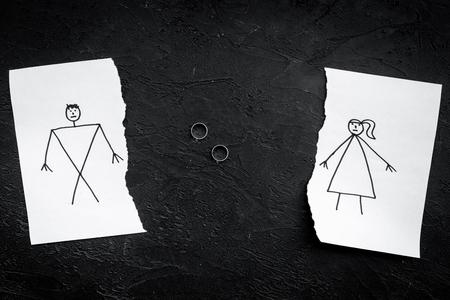 離婚または崩壊の概念。描かれた男女との紙の破れたシート、黒の背景のトップビュー上の部分の間の結婚指輪。