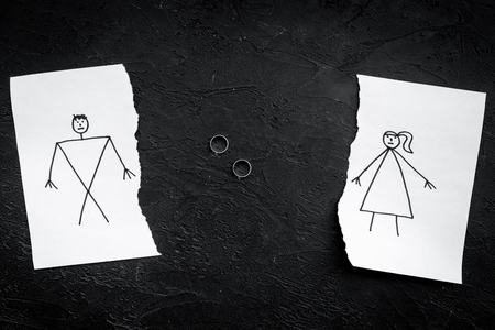 Divorce or falling apart concept. Torn sheet of paper with drawn man and woman, wedding rings between parts on black background top view. Banco de Imagens