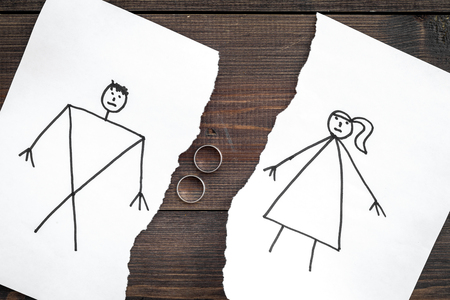 Divorce or falling apart concept. Torn sheet of paper with drawn man and woman, wedding rings between parts on dark wooden background top view.