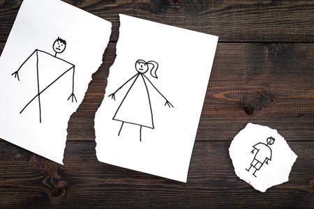 子供は離婚に苦しんでいる。暗い木製の背景の上面に描かれた男、女性と子供と紙の破れたシート。