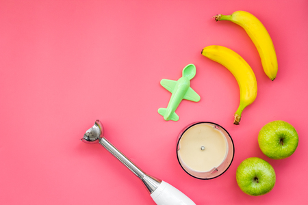 Homemade baby food. Cook puree with apple and banana with immersion blender. Pink background with toy top view space for text