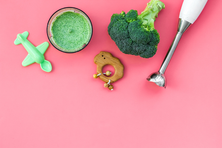 Homemade baby food. Cook puree with broccoli with immersion blender. Pink background with toy top view space for text Banco de Imagens