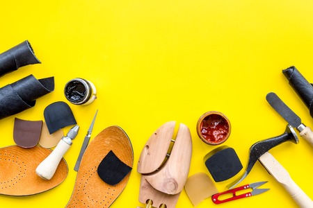 Clobber tools. Hummer, awl, knife, scissor, wooden shoe, paint and leather. Yellow background top view space for text