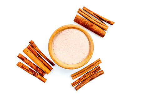 Cinnamon for cooking. Cinnamon sticks near bowl with sugar on white background top view copy space Banco de Imagens