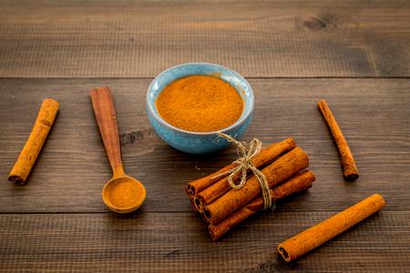 Cinnamon seasoning. Sticks and powder on dark wooden background copy space